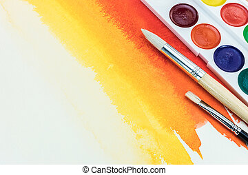 color palette with different brushes on red yellow watercolor background