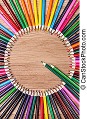 color pencils arranged in a circle on wooden background, top view