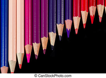 Color pencils in diagonal formation isolated on black warm palette