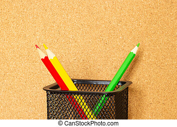 Color pencils on the background of a cork board, the concept of teaching in school