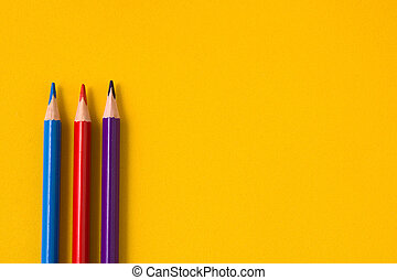 Color pencils on yellow background. Copyspace