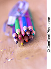 color pencils with ribbon and confetti bokeh