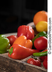Color peppers in a wooden tray.