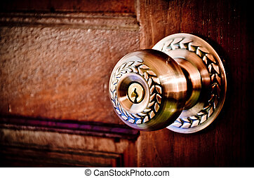 Color photo of a metal handle on a wooden door