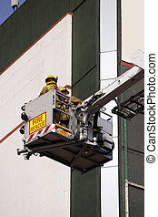 color photo of firefighter lifted in cherry picker in fire rescue