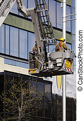 two firemen being lifted in cherry picker for rescue operation