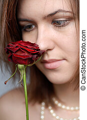 color portrait of woman looking at red rose