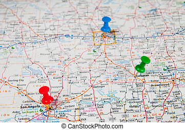 Color pushpins marking a location on a road map. Focused on...