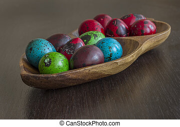 color quail eggs for holiday easter in a bowl on the table