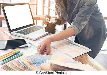 Color samples, colour chart, swatch sample, Graphic designer being selecting Color band and graphics tablet, pen at workplace with work example in camera and laptop on wooden desk