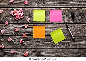 Color sticky note paper sheets with small hearts. Closeup on...