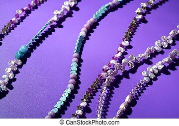 Color stones jewelry necklaces, purple background