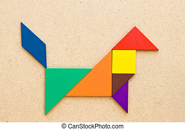 Color tangram in dog or wolf shape on wood background