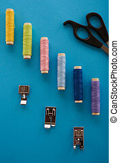 color thread, scissors and sewing the elements on top of a blue background