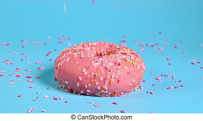 Color toppings sprinke on top of delicious pink donut on ...