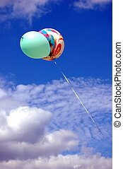 Colored balloons in the blue sky with clouds