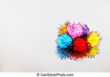 Colored beautiful pompons on a gray background