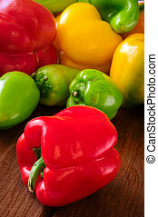 Colored bell peppers on wooden table - Colored bell peppers ...