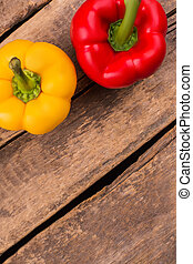 Colored bell peppers on wooden table.