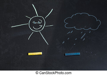 colored chalks, black blackboard with drawings of sun and a cloud