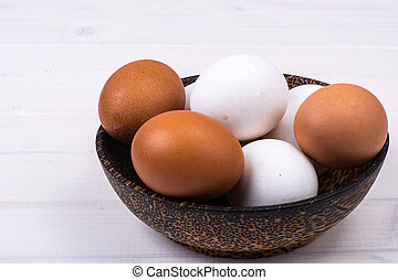 Colored chicken eggs in wooden bowl on white boards