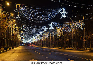 Colored Christmas lights and ornaments, stars and snowflakes in downtown of  Bucharest, Romania night time