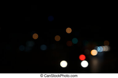 Colored circles bokeh of car lights at black dark night in city. Blurry abstract texture background.