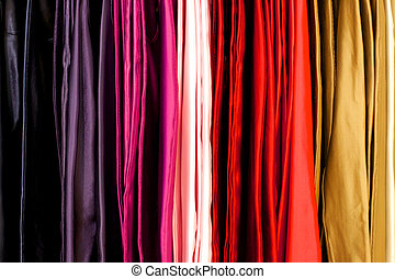 Colored Cloth - Cloth in many colors hangs from a rack at a...