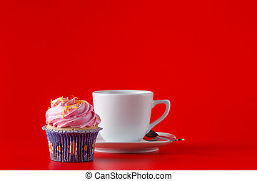 Colored cupcake with tea cup on brigth red background