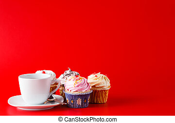 Sweet decoration. Cupcake with tea cup on brigth red background with copyspace