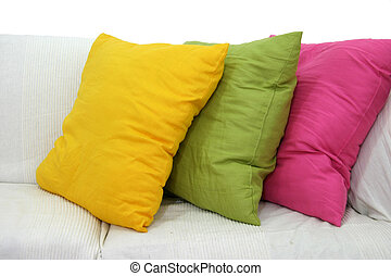 Three colored cushions on a white living room couch