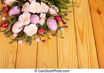 Colored easter eggs, candy, flowers, ribbon against backdrop pale wood.