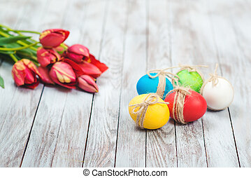Colored easter eggs, flower pot with green grass and beautiful tulips on wooden background.