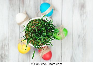Colored easter eggs, flower pot with green grass on wooden background. Top view.