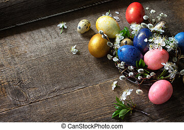 Colored Easter eggs in a nest with willow branches and spring flowers on a gray wooden background. Top view flat lay background. Copy space.