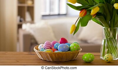 colored easter eggs in basket and flowers at home - easter,...