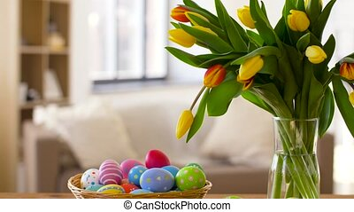 colored easter eggs in basket and flowers at home