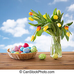 colored easter eggs in basket and flowers over sky