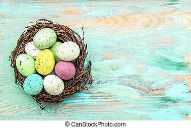 Colored easter eggs in nest on rustic wooden background