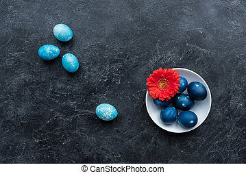 Colored Easter eggs in plate and on dark background
