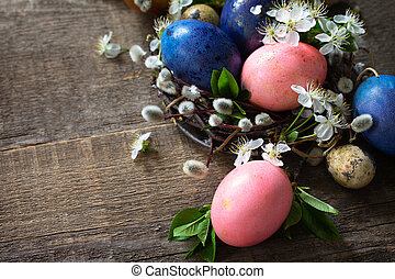 Colored Easter eggs in the nest with spring flowers on a gray wooden background. Copy space.