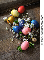 Colored Easter eggs in the nest with spring flowers on a gray wooden background.