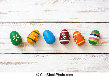 Colored easter eggs on white wooden background. Top view