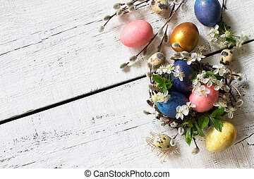 Colored Easter eggs, willow branches and spring flowers on a white wooden background. Top view flat lay background.