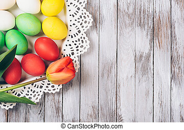 Colored easter eggs with tulips on a white wooden background.