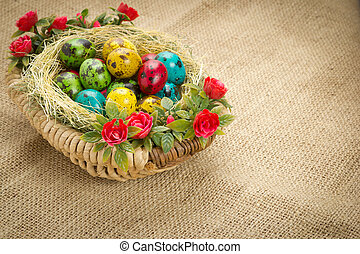 colored Easter quail eggs in a wicker basket