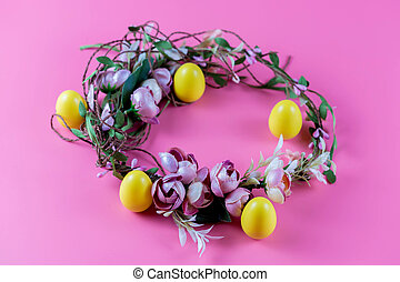 Colored Easter wreath and plastic eggs on a pink background