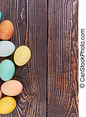 Colored eggs on brown wood.