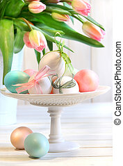 Colored eggs with bows and tulips for Easter