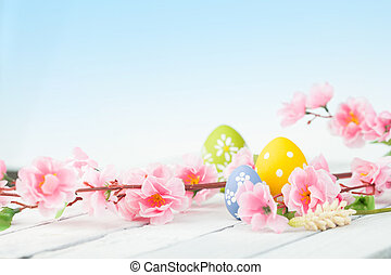 Colored eggs with pink flowers on white wooden background